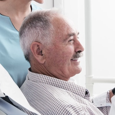 Older male patient sat in the dentist chair and smiling
