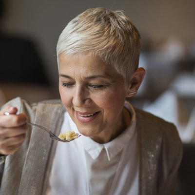 Older lady with short white hair, sitting down, and eating with a fork