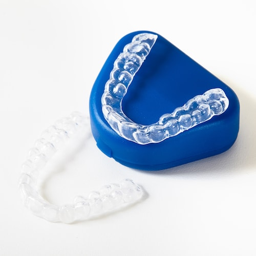 Two sets of Invisalign aligners with the blue case that the aligners arrive in