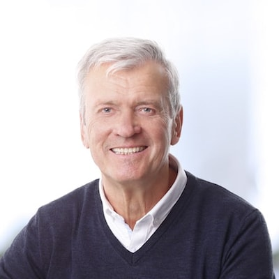 Older male patient wearing a shirt and sweater while smiling