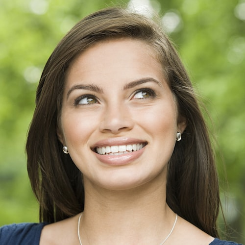 Beautiful woman looking to the side and smiling while wearing diamond earrings