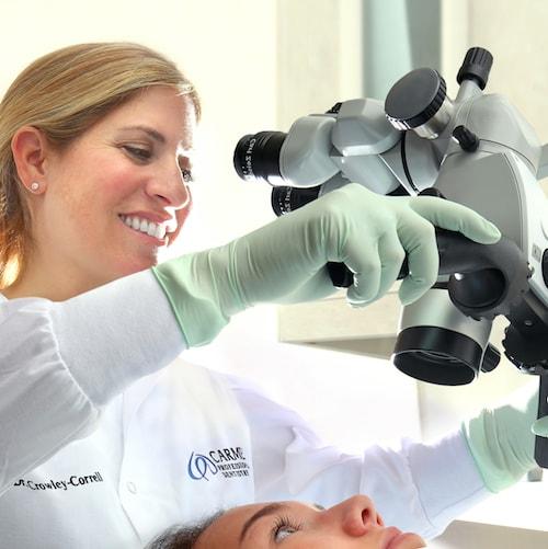 Dr. Carolyn Crowley Correll using dental technology equipment for a dental exam