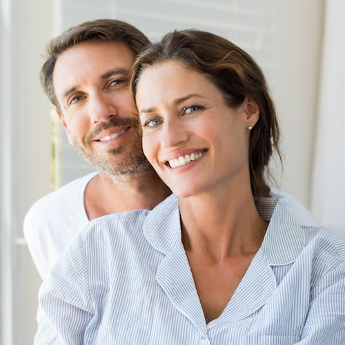 A woman stand in front of a man and they are both smiling