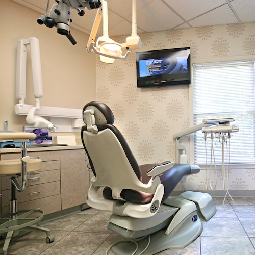 Our treatment room filled with dental equipment, a TV, and dentist chair