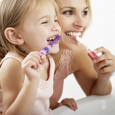 Little girl and her mom brushing their teeth and smiling