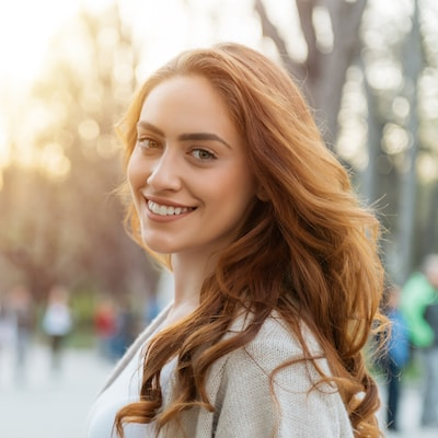 Woman with red hair looking back and smiling in a winter sweater
