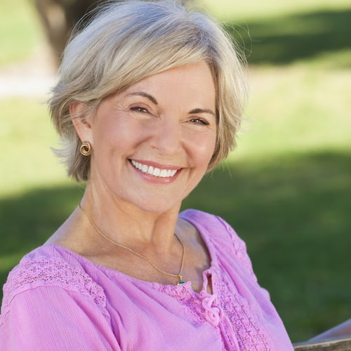 Older lady wearing a pink top and smiling while sat outside